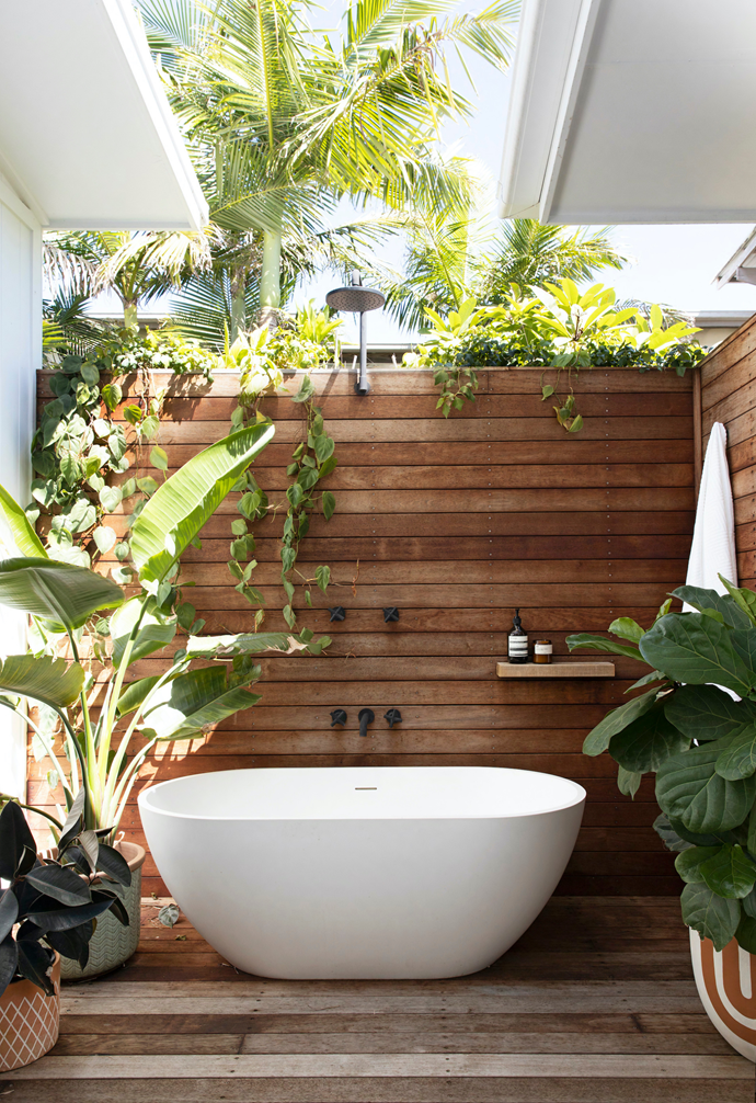 The guest bedroom at this coastal home in northern NSW includes a luxurious outdoor tub so visitors can soak under the stars. Timber screens provide plenty of privacy.