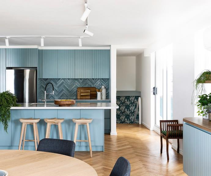 """An expanse of cabinetry and undulating splashback evokes the seaside setting of the six-bedroom home of Nicole, Evan and their daughter Charlotte. The choice of Taubmans November Rains, paired with Natucer 'Piastrella' splashback tiles from Academy Tiles, was deliberate, as the aim was for a palette """"neither bland nor over the top"""", according to Nicole. The island is topped with a Calacatta Luxe slab and Charlotte sits on a 'Tractor' bar stool from Uniqwa Collections."""