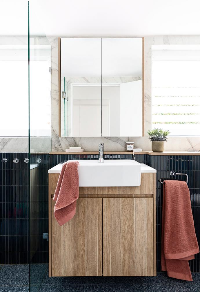 """An elegant navy scheme defines the couple's bathroom, with darkly dramatic Inax 'Biyusai' feature tiles from Artedomus and denim terrazzo floor tiles from Signorino Tiles. """"We wanted the master space to be almost like a hotel bathroom, where you walk in and go, 'Wow!'"""" says Nicole. """"The blue floor tiles make it feel kind of like you're walking on the ocean. We wanted that connection.""""'Calo' towels in Antique Pink from Country Road and a vanity made of Polytec 'Prime Oak' woodmatt introduce warmth into the zone. """"We didn't want it to be safe,"""" explains Nicole. """"We wanted it to be different."""""""