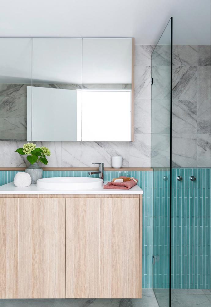 """""""Sometimes I think her space is better than ours – it's amazing!"""" marvels Nicole. Her daughter's gorgeous bathroom features Inax 'Arcaico Border' tiles in a summer-lovin' aqua shade from Artedomus and marble-look wall and floor tiles from Tiles By Kate. """"We wanted to continue the colour theme through the house,"""" says Nicole, adding that there's also plenty of storage here for Charlotte. """"In Singapore, there's not a lot of storage, and we really missed that, so that was a big part of the design brief."""""""