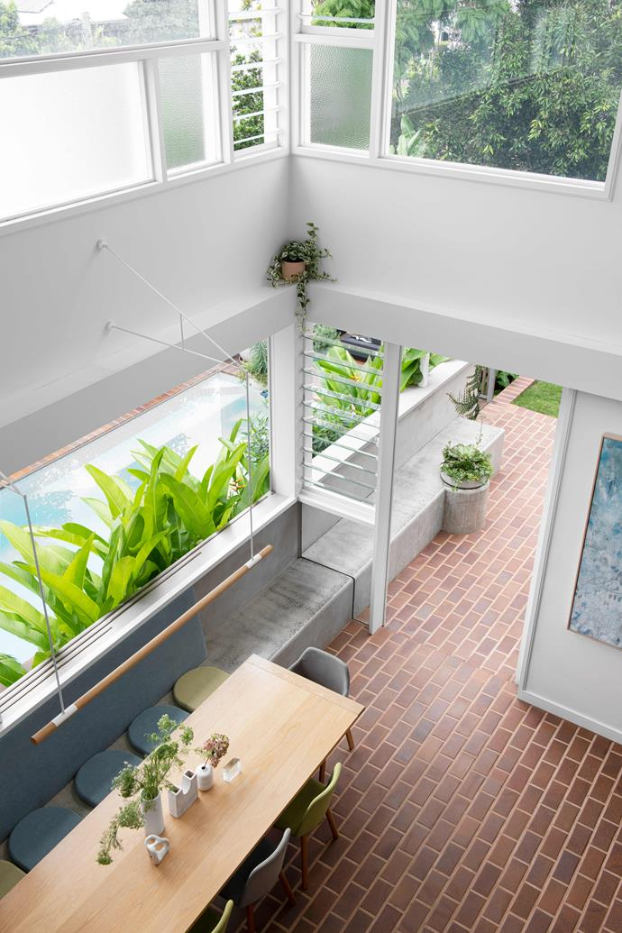 """Removing part of the first floor created this lofty open space over the dining zone. The design extends outside via the [built-in concrete seat](https://www.homestolove.com.au/concrete-design-ideas-20850