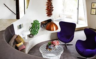 Mid-century retro sunken living room with two purple armchairs