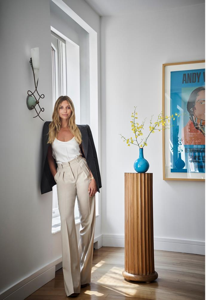 """""""With personal projects, I push myself to try new things, but the complete freedom can be tricky, versus when I'm working with a client, there's a more clear directive,"""" Jessica tells. """"And working for yourself means you're not on a deadline, so things can take much longer!"""" Here, she's pictured beside a decorative sconce from 1stDibs and an Andy Warhol artwork."""