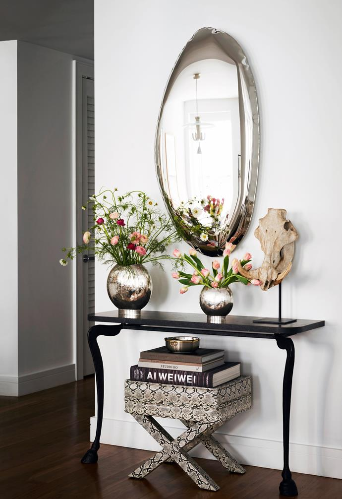 In the foyer is a Hoof console by Rose Uniacke and a Tafla 04 mirror by Zieta Prozessdesign from 1stDibs. The display is complete with a vintage Billy Baldwin python leather footstool and vintage '50s Dior vases.