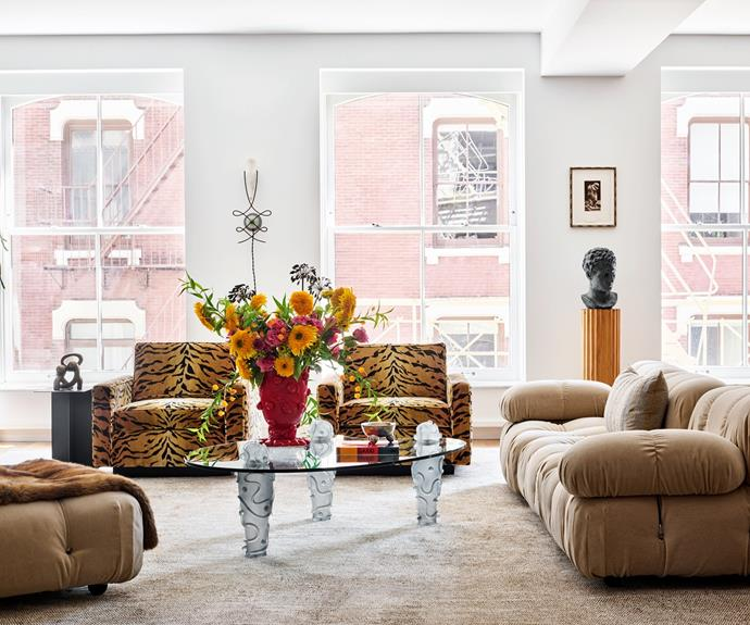 """""""I wanted to allow the unique pieces of furniture to each have their moment, but still talk to each other despite their diversity,"""" says homeowner and interior designer Jessica Schuster. Her loft apartment's living space is a perfect example, with its charismatic collection of vintage designs. She purchased the Mario Bellini 'Camaleonda' sofa at auction and had it reupholstered in mohair fabric. A pair of 1960s Harvey Probber club chairs make a bold impression in Clarence House 'Tanzania Tigre' fabric; so too does the bust from Casa Gusto on an Italian fluted wood pedestal from 1stDibs. The vintage Garouste & Bonetti coffee table informed the entire scheme. On top is a Gaetano Pesce 'Nugget' vase."""