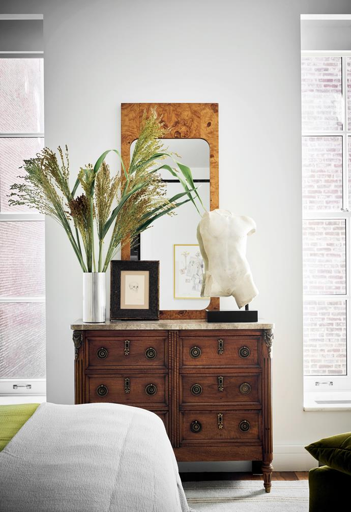 In the master bedroom is a Louis XVI-style dresser with a marble top. The burl wood mirror is by Milo Baughman and the plaster bust is vintage.