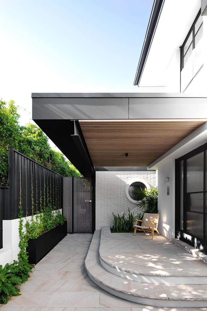 """**OUTDOOR AREA** Sandstone pavers at the front of the house offer a light contrast to the darker elements. The [round window](https://www.homestolove.com.au/house-window-styles-and-names-5514
