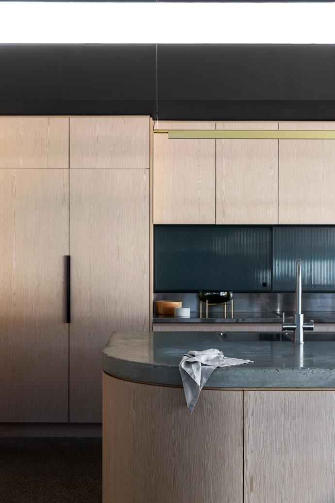 """Clever design elements in the new space range from the sculptural (the curved walls and concrete island bench) to the practical (rubbish chutes in the [butler's pantry](https://www.homestolove.com.au/butlers-pantry-design-ideas-17450