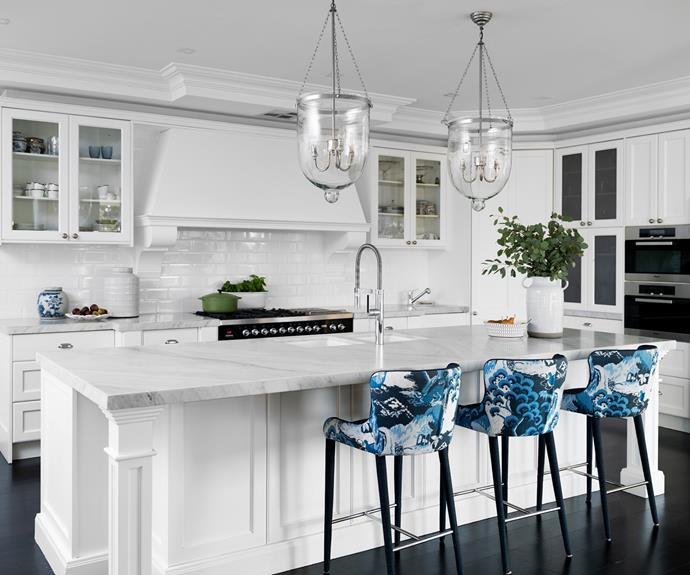 """""""Fortunately, the previous owners saved us the heartache of a major build,"""" says Sonja. Still, the stylist gave the kitchen a spruce up. 'The Regency' pendants from Home & Clan define the classic aesthetic, while the stools – upholstered in Robert Allen Road to Canton fabric – and Carrara marble benchtops are all stamped with Sonja's personality, as are the blue-and-white ceramic ginger jar, large white vase, and white milk jar from Sonja's store. Chic appliances include the Ilve stove, Miele wall oven and steamer and Liebherr fridge, all available at Winning Appliances."""