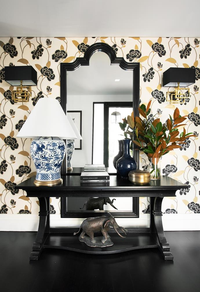 """Guests get a sense of this as soon as they step into the entrance. """"This wallpaper makes a statement and sets the scene for what lies beyond,"""" says Sonja. The Colefax and Fowler wallpaper is the perfect backdrop for a Ralph Lauren 'Foo Dog' table lamp, Eichholtz 'Windolf' sconce and Hamptons mirror, all from Sonja's store Home & Clan. """"With so much choice, I have to rein myself in,"""" she says. On the base of the Coco Republic console sits an Elephant Duke sculpture by artist Donald Greig. """"The French antique jardiniere was a second-hand find,"""" says Sonja."""