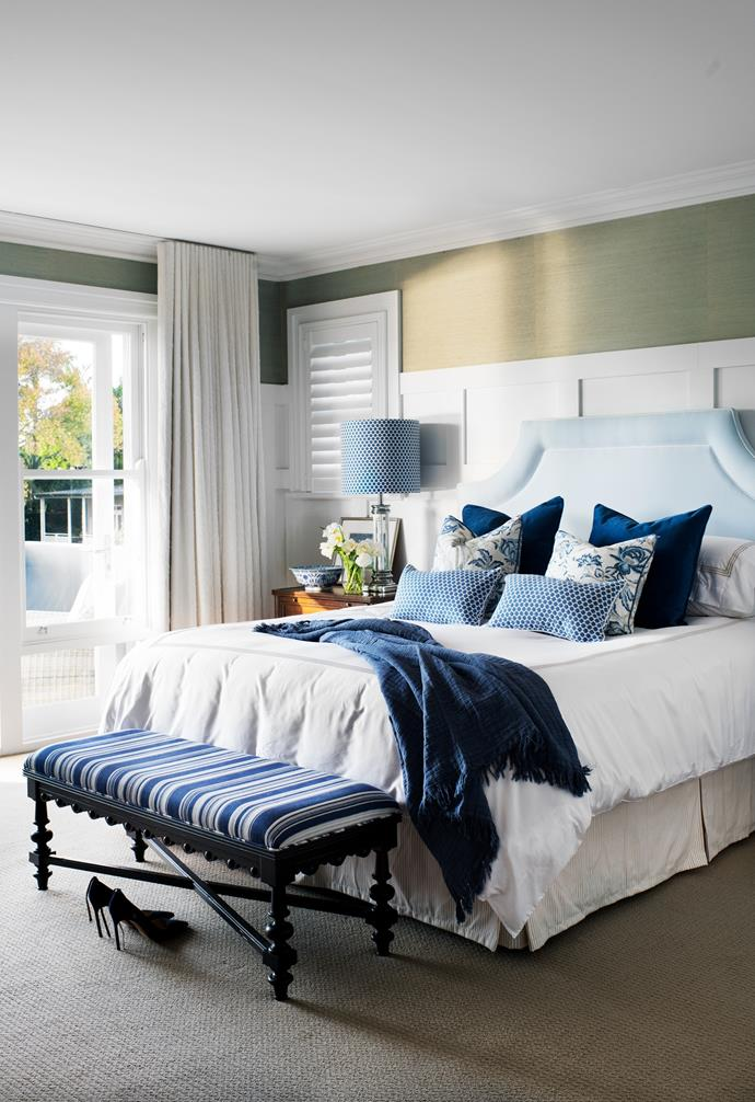 """""""It was important that it felt neither masculine or feminine,"""" says Sonja of the couple's bedroom. The Thibaut grasscloth wallpaper was originally sky blue but has since faded to this colour, which Sonja says she loves just as much. Sonja's favourite colour combination, blue and white, is celebrated in the ottoman, scatter cushions and the lampshade in Thibaut Bijou in Blue, all Home & Clan. The ice-blue bedhead, in fabric from Home & Clan's Designer range subtly links the rich blues with the neutral bed skirt, in Home & Clan's Signature Taupe fabric range"""