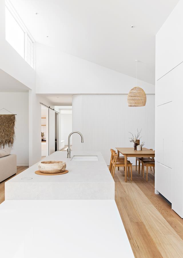 """Nestled between the living room, casual dining space and outdoor deck of this [coastal home](https://www.homestolove.com.au/coastal-new-build-newcastle-22209[ target=""""_blank""""), the sun-drenched kitchen is highly functional and designed with concealed features, such as a Point Pod pop-up power socket. It boasts a generous kitchen island with a low drop-down bench for young children and a butler's pantry."""