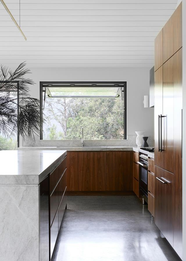"""""""There's a mix of contemporary and fine finishes with touches of rawness and natural elements,"""" says interior architect Phoebe Nicol of this [modern farmhouse](https://www.homestolove.com.au/modern-farmhouse-style-weekender-21723 target=""""_blank""""). In the kitchen, for example, the concrete floor and black steel rangehood are offset by joinery in a deep honey-toned timber veneer. A quartzite benchtop in beautiful toffee tones and soft veining, also brings warmth and texture to this space."""