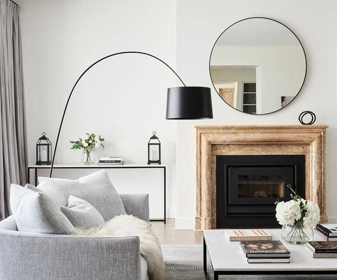 Living room with fireplace and large circular mirror