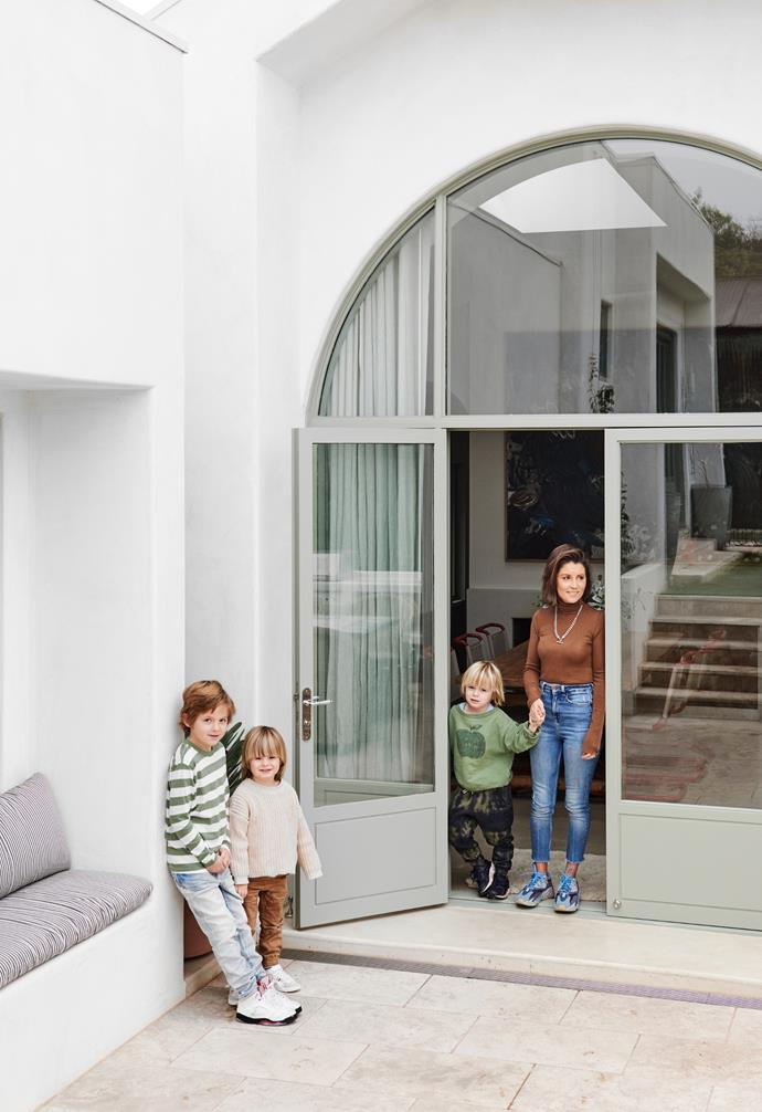 Humphry, Will, Louis and Phoebe stand at the oversized arched doors, which were designed by Lucy Bowen and lead to the travertine-paved entertaining area.