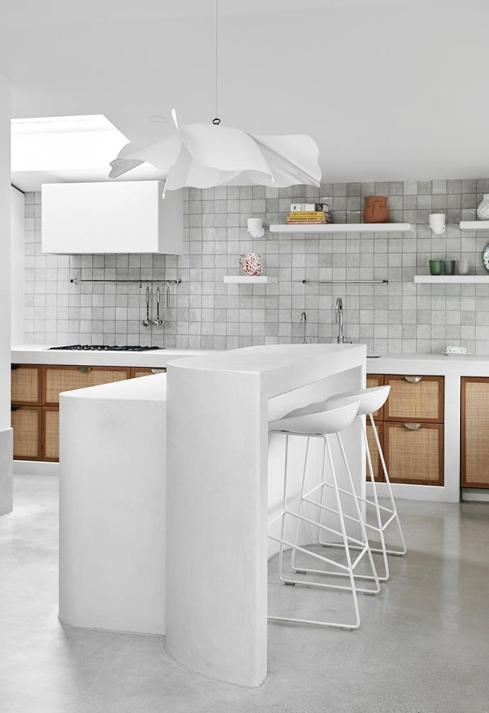 """Italian feature tiles, plaster-rendered benchtops and rattan-inset cabinetry give the kitchen a Santorini-style aesthetic. """"The Opinion Ciatti 'Papavero Raggiante' suspension lamp from Artemest is our favourite light fitting in the house,"""" Phoebe adds."""