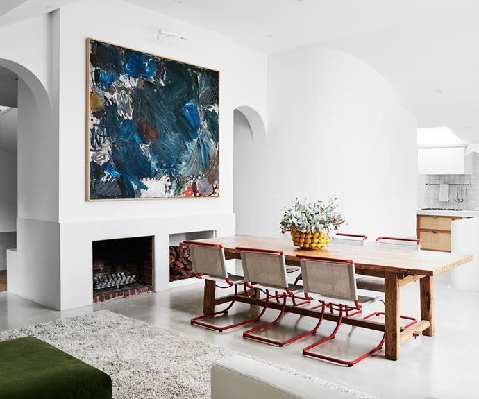"""For her home's floors, Phoebe experimented with different concrete colours to achieve the perfect warm grey. """" As an artist, colour is extremely important to me,"""" she explains. Meanwhile, the dining room, with its Fenton&Fenton table, Ludwig Mies van der Rohe chairs from Anibou and large artwork by Oscar Perry from The Commercial Gallery, symbolises everything she and George love about their house. """"The height of the ceilings, the shapes and the feel of this room are why we bought it to begin with, and it still has the same energy now,"""" Phoebe says."""