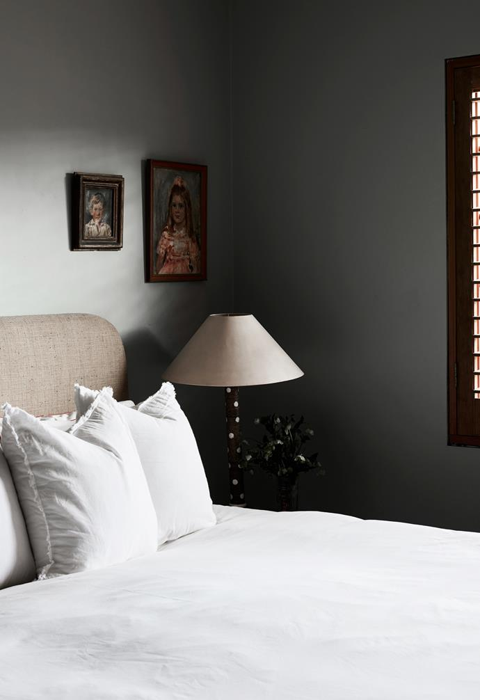 """""""For our bedroom, we tried to create a calm space to escape the kids,"""" adds Phoebe. She custom-made the textural woven bedhead and painted the walls in Alto Paints First Light. The bedlinen is from Ikea, the vintage table lamp was bought at auction and the portraits are by James Govett."""