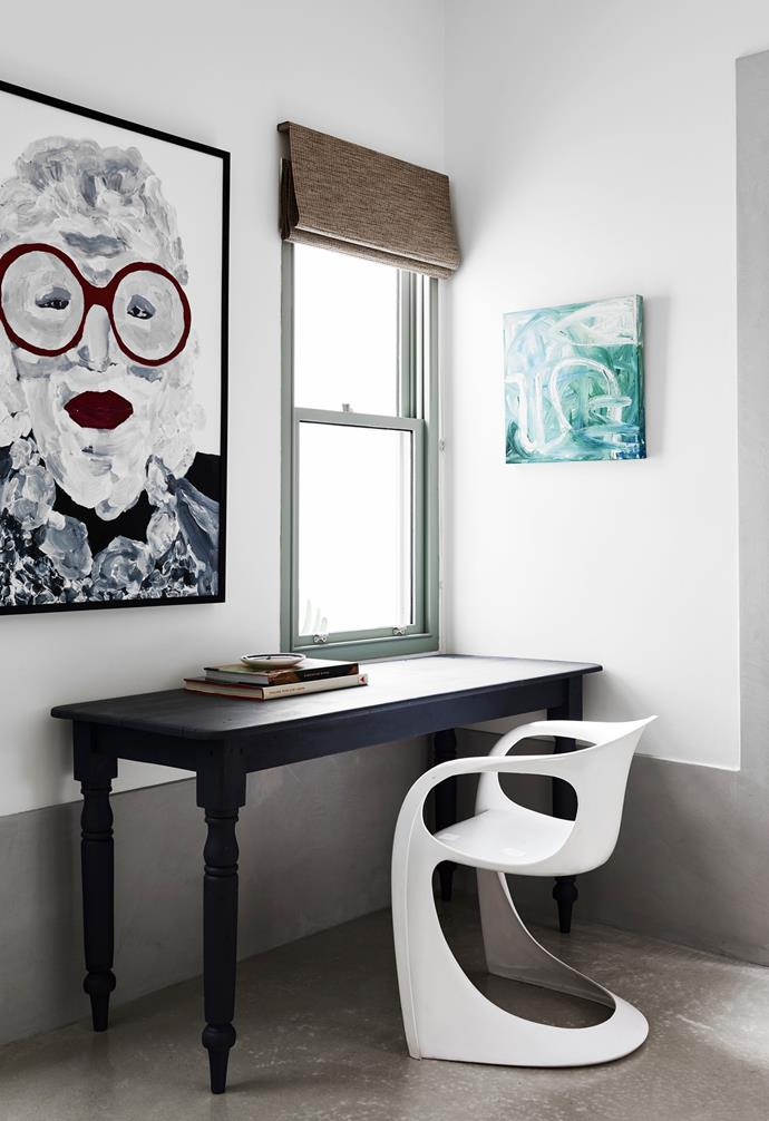 """A corner of the living area has been utilised as a work space. """"The desk is an old table that my mum cut down as a desk for us,"""" Phoebe says. The larger portrait of Iris Apfel is by Kate Carnegie."""