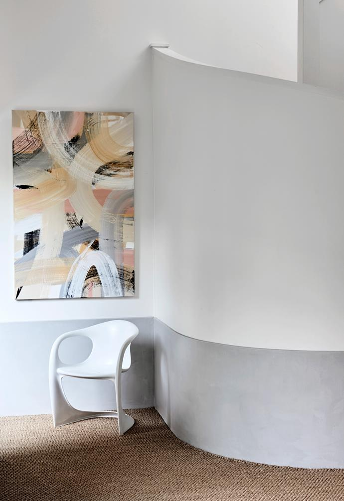 """""""The entry is the breathing space of the house – not overly functional but a beautiful place to hang artworks and look into the front courtyard by Andrew Panton Design,"""" Phoebe explains. """"Lucy drew inspiration from the existing curved staircase and took my brief of soft edges and indented shelving and ran with it."""" The artwork is one of Phoebe's pieces, the sisal carpet is from International Floor Coverings and the Casala chair was bought at auction from Leonard Joel."""