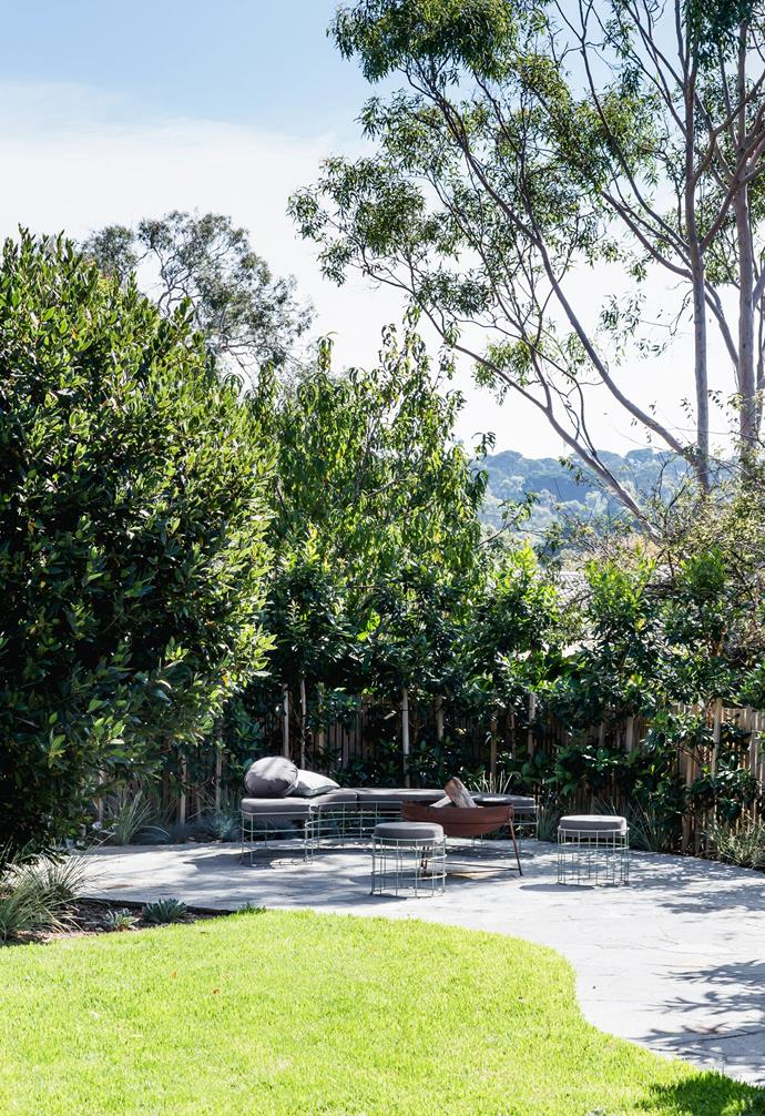 Shaded by a towering gum tree, this cleverly reconfigured area of the garden is now centred around a fire pit and an 'Ellis' curved bench with matching ottomans from Grazia & Co. And as the family can attest, it's the perfect spot to take time out under the stars when the temperature drops. The round cushion is from The Artisan Storeroom.