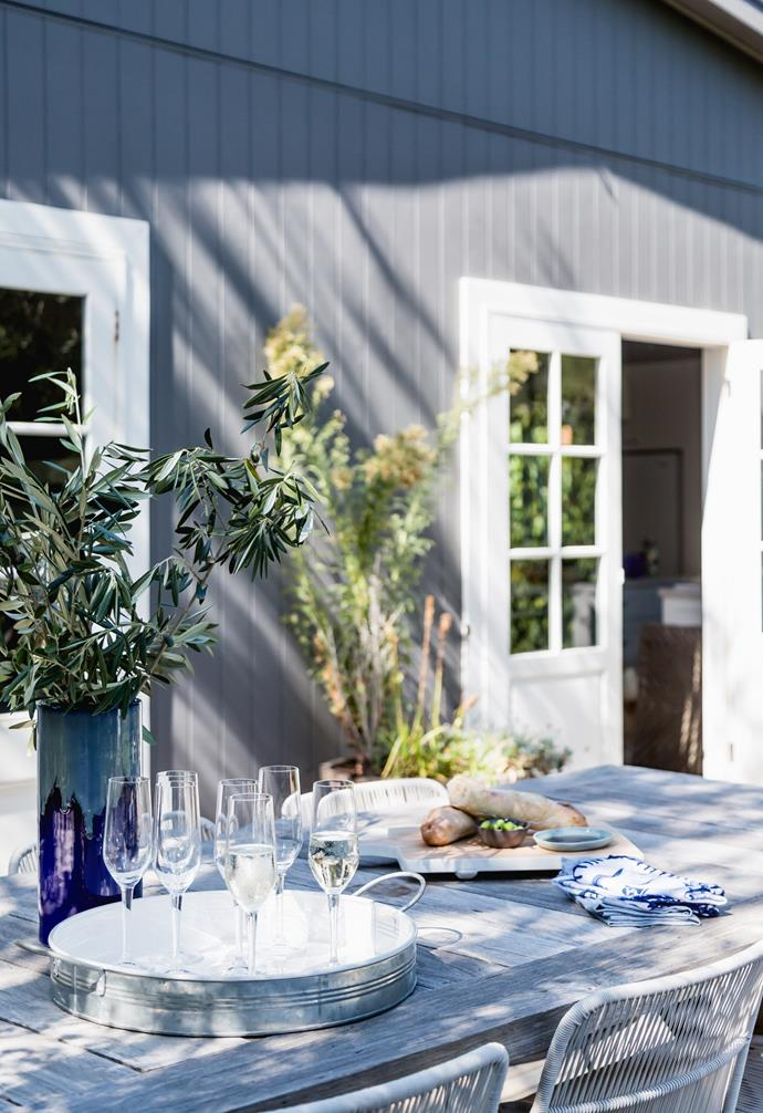 An entertaining deck overlooks the garden, with chairs from Globe West, Luigi Bormioli glasses from David Jones and napkins from Myer and Linen Moore. Get the look of a farmhouse-style dining table from Eureka Street Furniture.