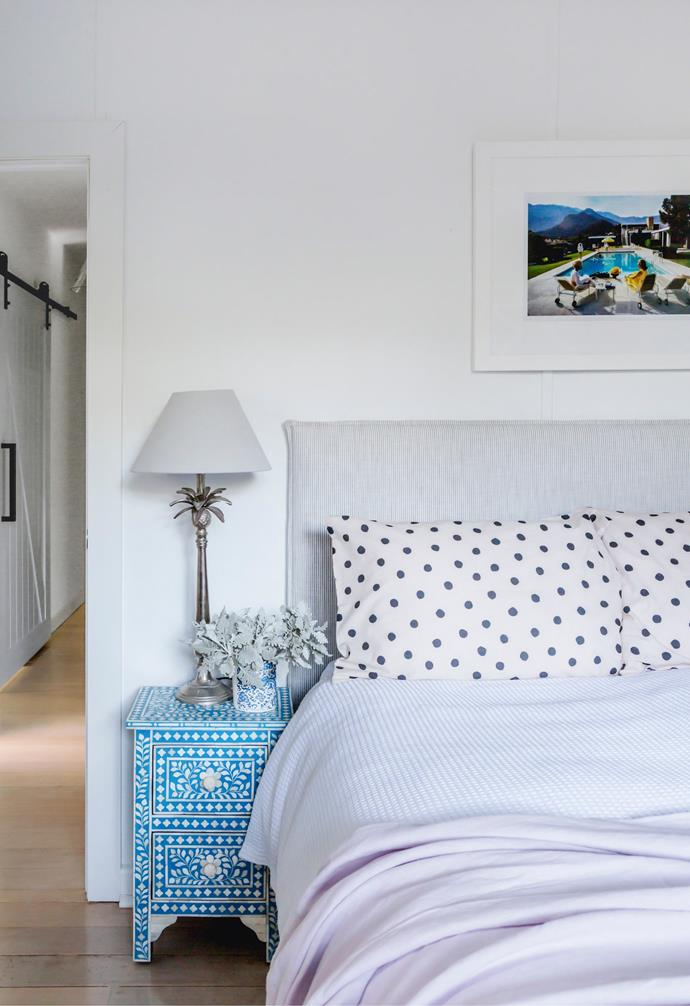 In the guest bedroom, a 'Poolside Gossip' photographic print by Slim Aarons from Fineprint Co claims pride of place, just ahead of a side table from HH Collective.