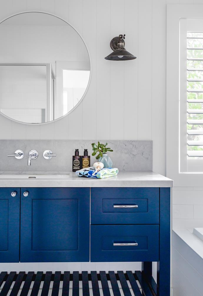 """With its striking vanity unit in two-pac Dulux Blue Accolade and Caesarstone Noble Grey – not to mention the detailed Hardiegroove wall lining by James Hardie – there's much to admire in the family bathroom. """"I love the navy joinery against the white walls,"""" says Belinda. """"Blue and white is a classic pairing."""" An oversized circular mirror and Dorf tapware from Reece also make a style statement. Belinda sourced the vanity pulls and knobs from US company RH."""