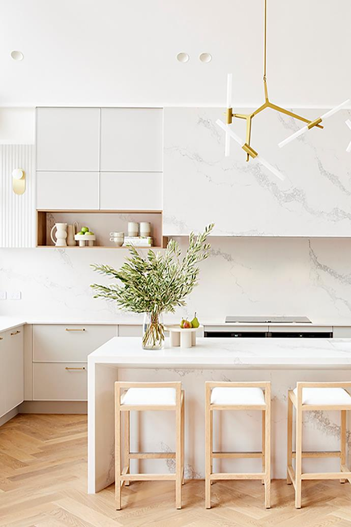 """Caesarstone in 'Statuario Maximus' features throughout Ronnie and Georgia's light-filled kitchen. 'Spear 6' light pendant, [Micah Lighting](https://www.micalighting.com.au/spear-6-light-pendant-gold-matt.html