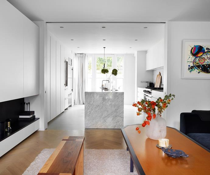 """A family room with a low veneer [coffee table](https://www.homestolove.com.au/coffee-table-living-room-ideas-22666 target=""""_blank"""") by Francois Dumas flows into the adjoining kitchen. """"As a family, we often spend time in the open kitchen space, where cooking, homework, reading and lounging all happens concurrently and brings us together after a day of school or work,"""" Nathalie tells."""