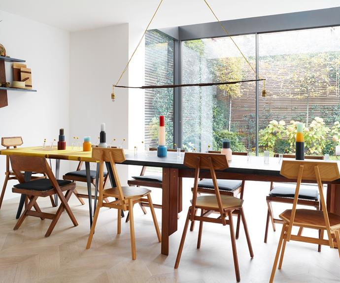"""A new double-height extension houses the [dining room](https://www.homestolove.com.au/dining-rooms-5533 target=""""_blank""""). Nathalie commissioned the table by Martino Gamper and Friends for a SEEDS show in 2016 and has paired it with Tiago Almeida and vintage Pierre Jeanneret chairs. Pillar candles by Lex Pott are dotted along the table's surface, lit from above by a slender Franz West pendant. """"The children understand that it's important not to destroy things around them; that we have to be careful but not too precious,"""" Nathalie explains."""