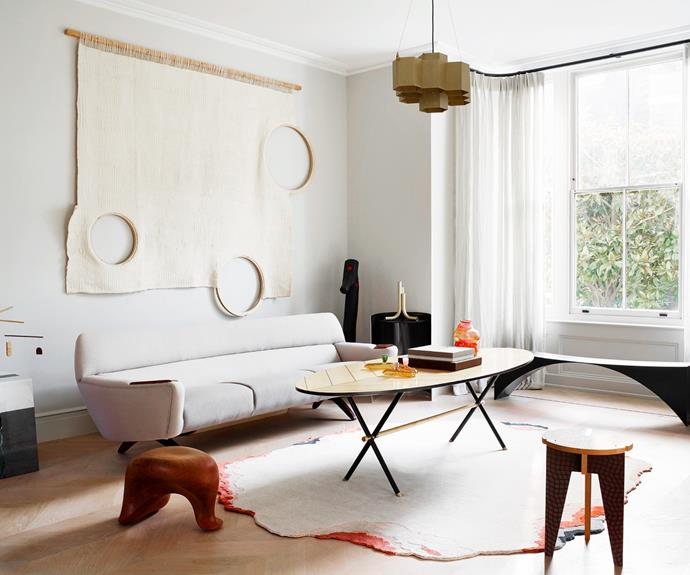 """The home's ground floor was opened up to create flexible zones that double as both gallery and family spaces. The wall hanging is by Soojin Kang and the maple and iron Piuma table was commissioned from Pietro Russo, who also designed the Metropolis pendant. The vintage sofa is by Leif Hansen, the low stool on the left is by Aldo Bakker and the angular stool on the right is by EDHV. In a corner of the same space, spiral stair shelving by Pietro Russo was inspired by the """"strength and endurance"""" of the Ginkgo tree."""