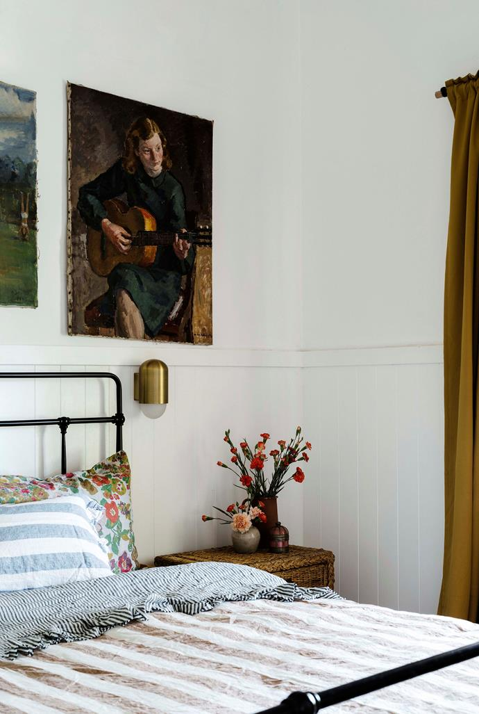 Emma and Matt's bedroom has a collection of oil paintings above the bed. The bedding is from Society of Wanderers.