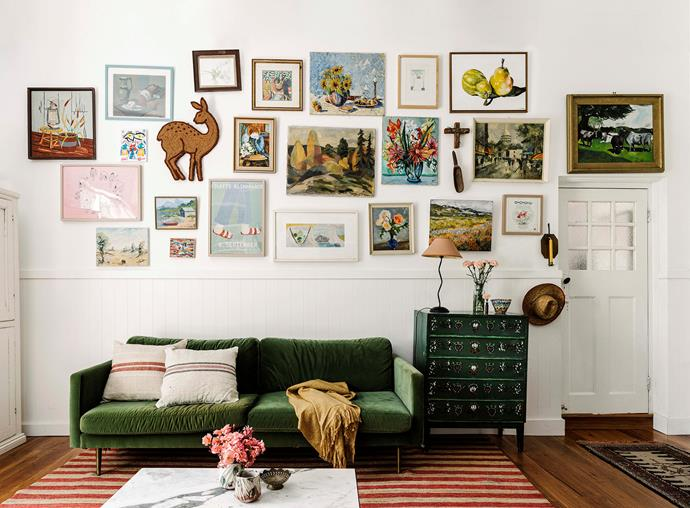 Matt Blatt's Big Apple velvet sofa in emerald green sits below the gallery wall, which includes family artwork and pieces found on travels.