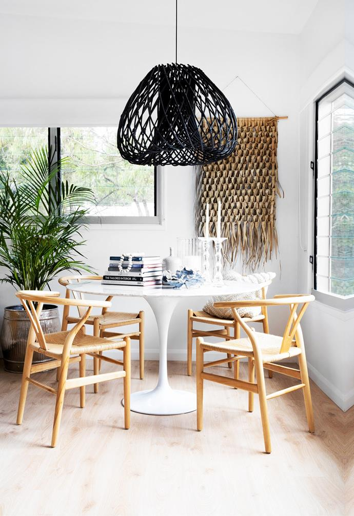 In the reading area, assorted pieces and textural layers include a Matt Blatt dining table, chairs from Provincial Home Living, coral from Coastal Vintage and a woven wall hanging from Marmoset Found. The silver drum is from Orson & Blake and the black pendant light was sourced from Eclectic Style.