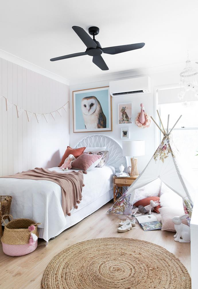 """The couple's youngest daughter requested a pink bedroom. Rather than a bright candy hue which might fall out of favour, Amber defined a VJ feature wall in Dulux Mornington Half, which creates a subtle dusty pink backdrop. """"It's a colour that won't date and, teamed with accessories in shades of blush and rust, it's soft and serene,"""" she says. Many pieces, including the 'Bahama' cane bedhead, linen, scatter cushions, flamingo head, rabbit print and Fleur Harris tepee, were sourced from Adairs, while the owl print is from Eclectic Style and the small drawing was found at Eumundi Markets. Textural elements such as the cane bedside table, also from Eclectic Style, and a Beacon Lighting rattan lamp add a lovely sense of warmth. For a similar black overhead fan, try Bunnings."""