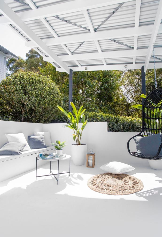 Originally painted mission brown with black aluminium fencing, the pool area was in desperate need of an update. Inspired by stays at Halcyon House hotel at Cabarita on the NSW far north coast, Amber channelled holiday vibes to produce her very own poolside retreat. Concrete walls and floors were lavished with Dulux Casper White Quarter, while cushions from Eclectic Style and Adairs were scattered to add comfort atop a storage bench seat. The hanging rattan chair, also from Eclectic Style, was customised with a lick of black paint. A coffee table from Bunnings keeps light refreshments and weekend reading in easy reach.