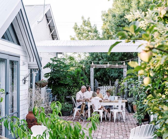 Family dining outdoors in brick courtyard