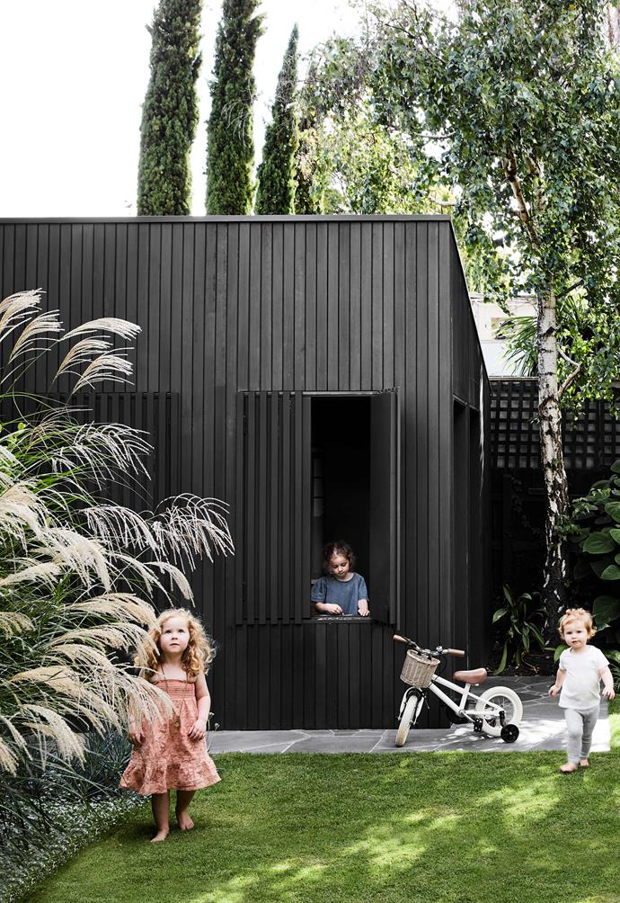 **GARDEN** Owners Sarah and Nick chose to extend upwards and widthways in order to keep their beautiful garden intact. The shed and rear facade are clad in cedar that's been painted low-maintenance black to make the green grass pop.
