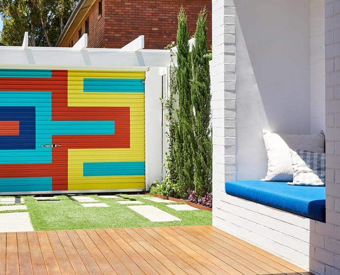 **BACKYARD** Lawn and pavers mix it up in the approach to the family's spectacular garage door, painted by artist Claudia Damichi.