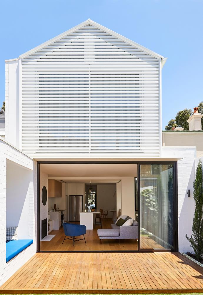 """BACKYARD (both pages) """"We loved the textures and features of the exterior, so having a simple white palette was a great way to show them off,"""" says Zander The wall and trim is Dulux Vivid White and the decking is blackbutt finished with a natural oil. Trees, Italian cypress and Eumundi quandong."""