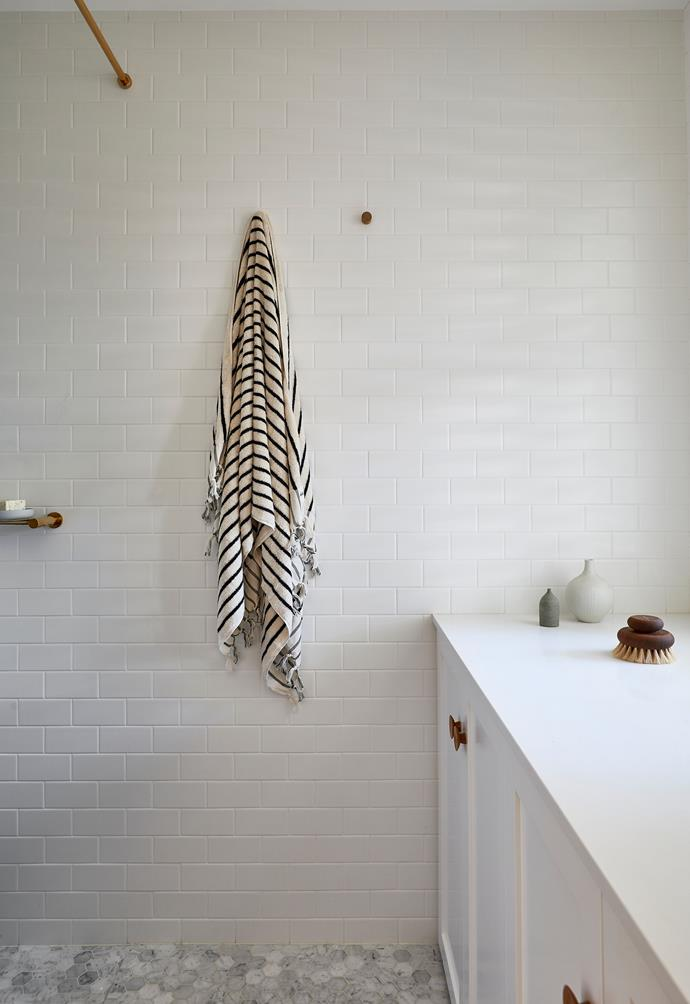 **BATHROOM/LAUNDRY** The walls are lined with matt-white ceramic tiles and the floor tiles are hexagonal Carrara marble mosaics, both from Surface Gallery. Cabinetry by Wilmont Joinery.