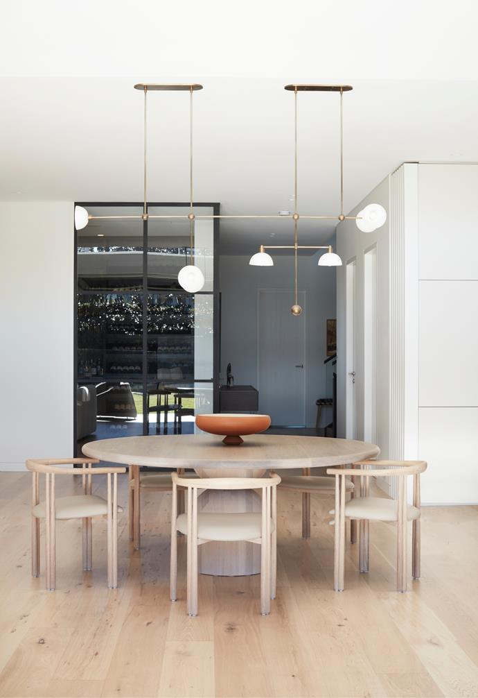 The dining area has a 'Bell' table from The Wood Room and De La Espada 'Elliot' chairs from Criteria under an Apparatus 'Trapeze 7' pendant light, also from Criteria. Bowl on table from Space. Cappellini 'Hi-Pad' stools from Cult.