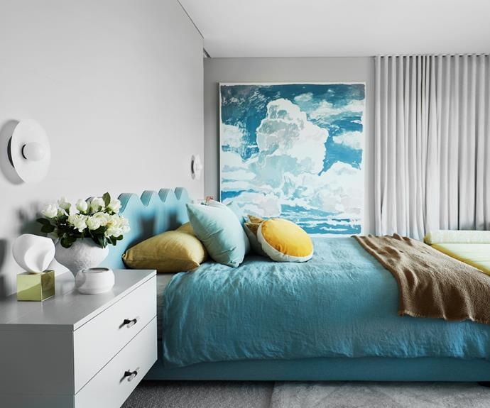 Blue hues create a serene mood in the master bedroom. Custom bed, bedhead and ottoman by Hugh-Jones Mackintosh. 'Petit Swoon' chair from Great Dane. On bedside table, Aerin sculpture from Palmer & Penn and vase by Katarina Wells from Curatorial+Co. India Mahdavi 'Bonbon' round cushion in Yellow from Studio ALM. Society Limonta throw from Ondene. Bed linen from Hale Mercantile Co. Curtains by Simple Studio. Artwork by Clara Adolphs from Chalk Horse.