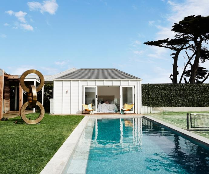 A backyard swimming pool with a pool house