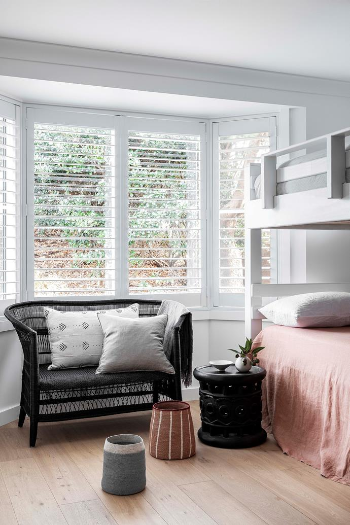 A bay window floods the bunk room with natural light.