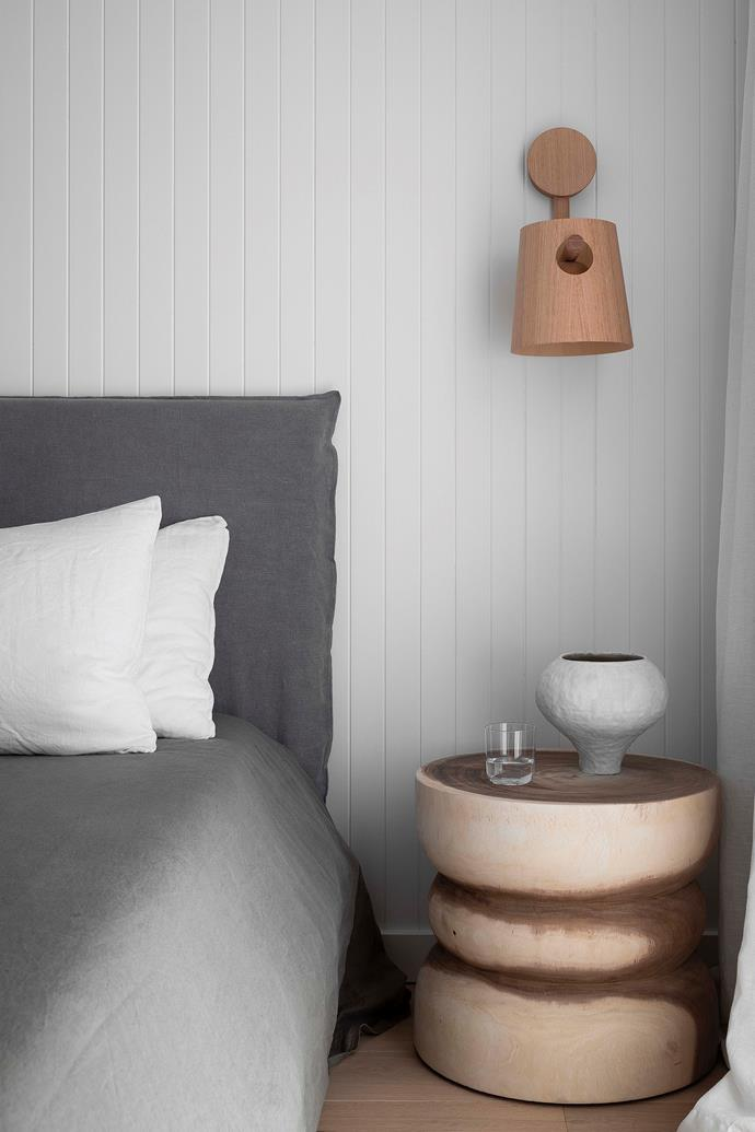 """A palette of grey and white gives the bedroom a serene atmosphere. 'Ghana' side table, [UniqwaCollections](https://uniqwacollections.com.au/products/ghana-side-table-natural