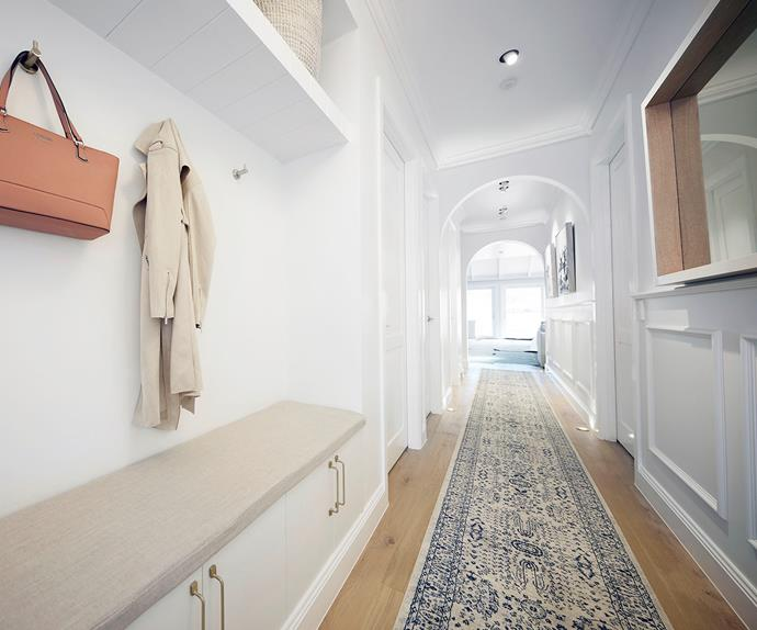 Classic Hamptons style hallway with arches and a storage bench
