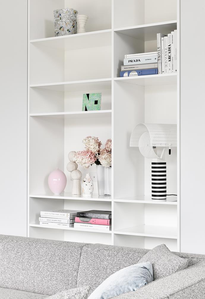 The shelving unit has compartments of varying sizes, framing the many knick-knacks.