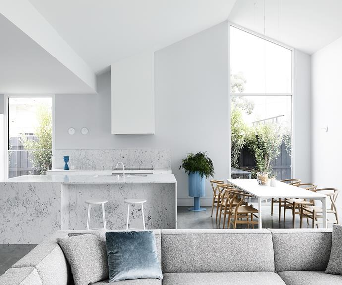 ale blue accessories, including velvet cushions from Poliform and a plant holder by Studio Ciao, complement the cool grey tones; the minimalist bar stools from Kin Design tuck away neatly.